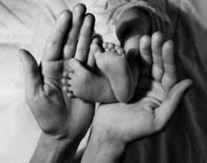Dziecięce stópki w dłoniach rodzica